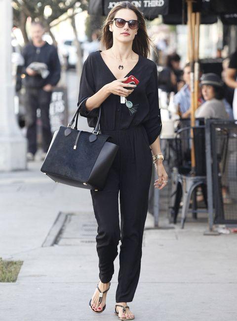 <p>La modelo <strong>Alessandra Ambrosio</strong> luce su mono negro en un street style de libro con sandalias planas, bolso de piel y joyas doradas.</p>