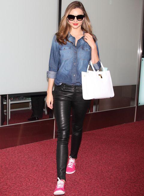 <p>Domina el street style pero también las terminales de los aeropuertos. De 10<strong>Miranda Kerr</strong> y su look con pantalones de piel negros, camisa denim, zapatillas rosa flúor y bolso blanco. Si la imitas, volarás cómoda y estilosa.</p>