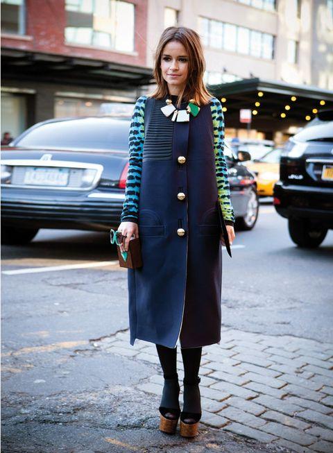 <p>Con un abrigo azul 'navy', mangas reptileras y zancos de corcho 'xxl'.</p>