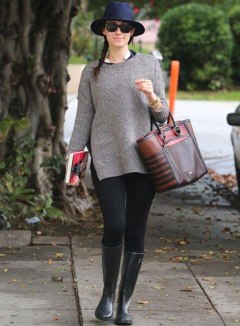 <p>Para los días de lluvia, nada como este look de <strong>Emmy Rossum</strong> con jersey oversize más camisa, leggings negros, katiuskas lisas del mismo color, sombrero azul navy y bolso de mano bicolor.</p>