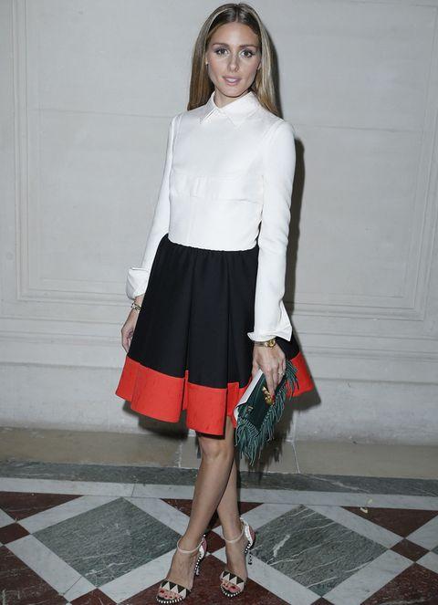 <p>La it girl <strong>Olivia Palermo</strong> lució un elegante outfit con camisa blanca, falda bicolor en negro y rojo, clutch de flecos y unas sandalias de print geométrico que suele lucir a menudo.</p>
