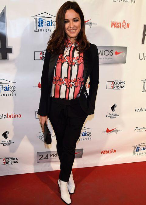 <p><strong>Verónica Sánchez</strong> apostó por un traje negro combinado con una camisa con print de rayas y flores, botines blancos y clutch negro.</p>