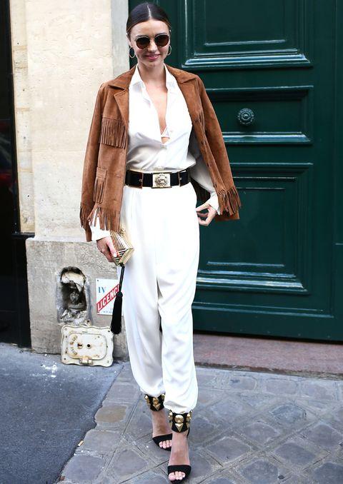 <p><strong>Miranda Kerr</strong> no renuncia al glamour y combina su look en blanco con un cazadora de flecos, sandalias al tobillo con detalles en dorado y clutch de este último color.</p>