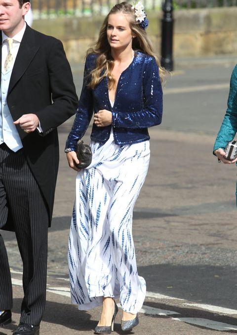 <p>Para asistir a una boda Cressida apuesta por un vestido largo estampado en azul y blanco y acpmpañado por una chaqueta de paillettes en azul, accesorios metalizados y tocado de flores.</p>