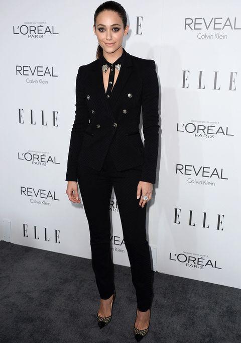 <p><strong>Emmy Rossum</strong> dejó a un lado los vestidos y escogió un traje negro con llamativos botones y aberturas de&nbsp&#x3B;<strong>Versace</strong>. Lo combinó con unos salones estampados de <strong>Louboutin</strong>.&nbsp&#x3B;</p>