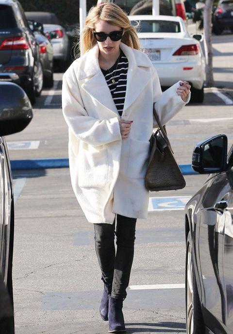 <p><strong>Emma Roberts</strong> apuesta por un abrigo blanco oversize, camiseta navy, pitillos en gris, botines morados y bolso de piel negro.</p>