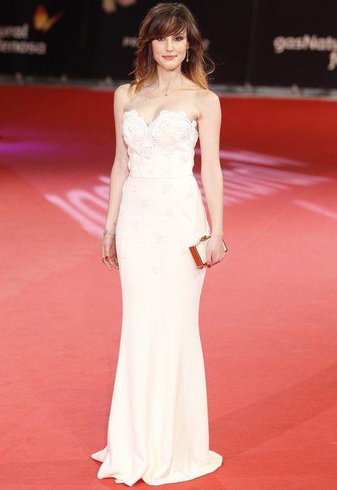 <p>Espectacular&nbsp;en la alfombra roja de la primera edición de los Premios Feroz con un vestido en blanco roto de escote corazón con cuerpo bordado que combinó con un clutch también en blanco y dorado.</p>