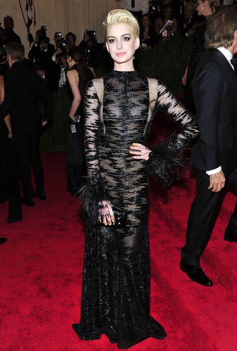 <p>Con un nuevo look de rubia platino vimos a <strong>Anne Hathaway</strong>. Vestida con un <strong>Valentino Couture</strong> vintage negro con bordado en zig zag semitransparente, detalles de strass y plumas en los puñós, y un clutch del mismo color y de la misma firma como único accesorio.</p>