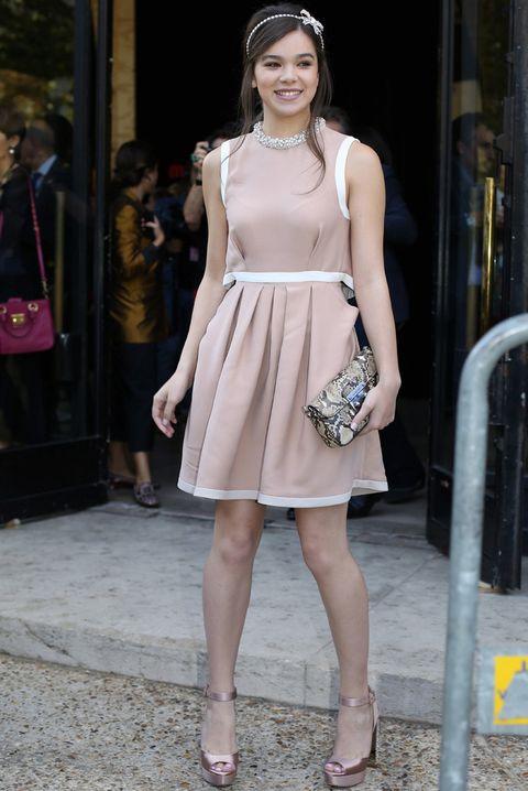 <p>En el mismo desfile vimos a <strong>Hailee Steinfeld</strong> con un look muy apropiado: minivestido rosa y blanco con cuello joya, sandalias metalizadas en rosa, clutch de print de pitón y una diadema joya con lazo.</p>
