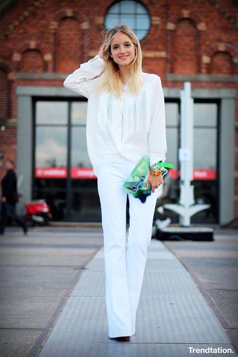 <p>Charlotte apuesta por un total look blanco, con blusa de flecos y pantalones acampanados. Como bolso escoge un clutch de Christpher Kane, de PVC relleno de líquido multicolor. El bolso ideal para salirse de lo convencional.</p>