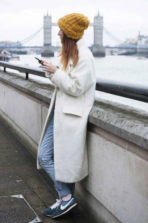<p>'Jeans' con dobladillo, abrigo largo en tono blanco, gorro de lana y deportivas Nike.</p>