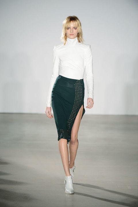 <p>Nos encanta esta falda tubo con abertura lateral y franjas de tachuelas. El top blanco de cuello vuelto y forma en los hombros equilibra el look.</p>