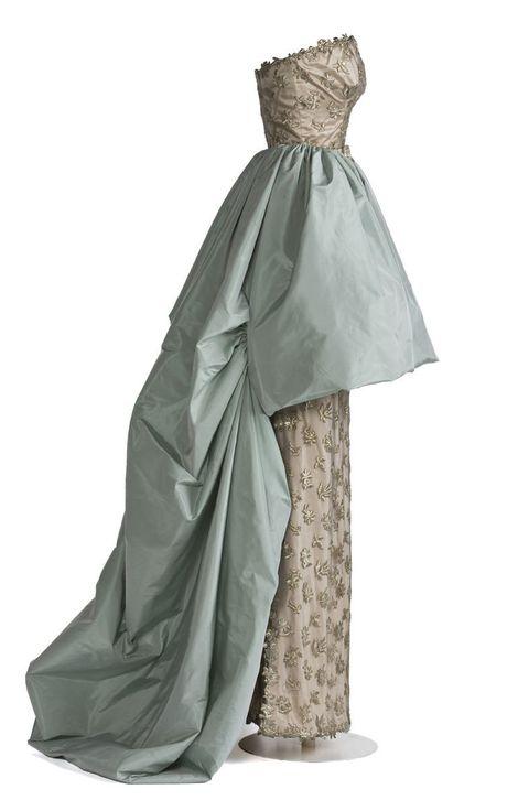 <p>Se trata de una de las 20 piezas que se han trasladado de forma temporal al <strong>Museo del Traje de Madrid.</strong></p><p>Un vestido largo, con escote palabra de honor en tul de algodón sobre tejido de raso de rayón beis, y decoración floral bordada en hilo metálico. La sobrefalda en tejido de tafetán de seda azul verdoso, servía también como capa.</p>
