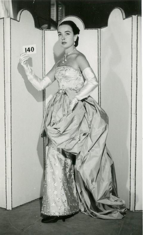<p>Esta fotografía inmortaliza a una modelo de la época, que luce uno de los vestidos icónicos de <strong>Balenciaga</strong>. Confeccionado en 1951, se trata de una pieza muy admirada porque está inspirada en el vestido que vemos en la obra del pintor&nbsp&#x3B;<strong>Francisco de Zurbarán, '</strong><strong>Santa Isabel de Portugal'</strong>&nbsp&#x3B;(Museo Nacional del Prado).</p>