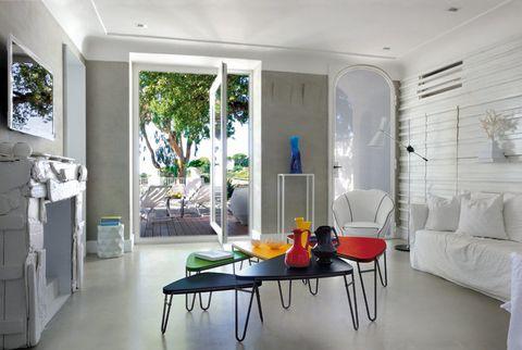 <p>Una base neutra en las paredes y el suelo son el marco idóneo para realzar escogidas piezas coloristas, como objetos vintage años 50 y las mesas de café Petal, diseñadas en 1951 por Charlotte Perriand y reeditadas por Cassina. Los sofás de lino en color blanco fueron diseñados por Paola Navone para la firma Gervasoni.</p>