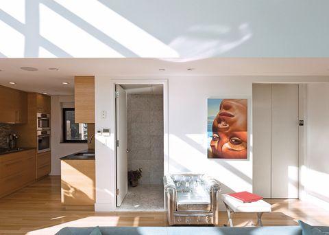 <p>Piezas reinventadas, como un sillón de corte clásico plateado, en Modani, o un retrato de Richard Phillips, marcan la diferencia en la entrada. Al lado, la cocina, en roble y con encimera de granito negro.</p>