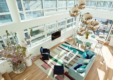 <p>Desde la planta superior se divisa la terraza, el comedor y el salón. En este último, destaca una divertida alfombra, mod. <i>Family,</i> de Novogratz, la primera colección de accesorios que lanzan los diseñadores. Sobre ella, un elegante y moderno sofá celeste, de Cappellini, con cojines en tonos azules, en Modani. Se complementa con dos butacas y una mesa de centro antiguas, en Adelaide.</p>