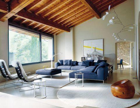 <p>Todo el salón está protagonizado por el sistema de asientos <i>Frank,</i> de Antonio Citterio, y la librería <i>Shelf,</i> de Naoto Fukasawa, ambos para B&amp;B Italia. La lámpara es de Artemide y la alfombra de Alberto Levi Gallery. La obra colgante, de Valentino Vago (Galleria Morone).</p>