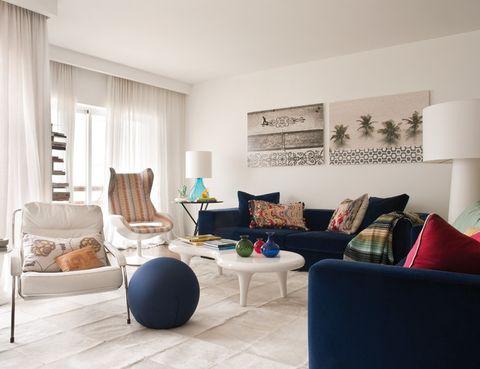 <p>En blancos y azules: butaca Maggiolina, de Marco Zanuso para Zanotta, y puf redondo, de Baleni. En la pared, fotos del artista brasileño Bruno Veiga.</p>