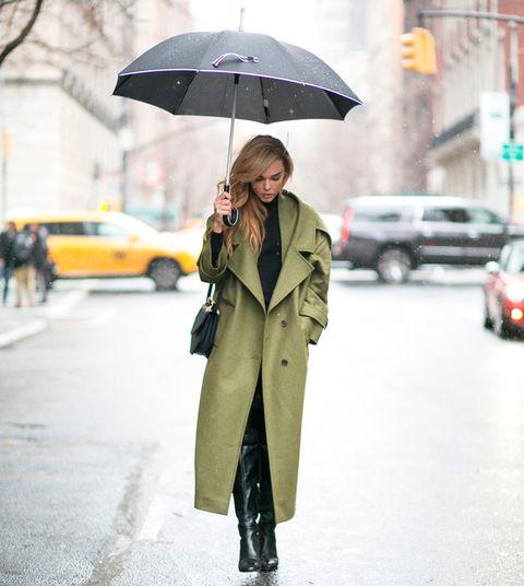 <p>Una gabardina verde larga sobre pantalones y botas negras, y un paraguas. Sencillez y estilo.</p>