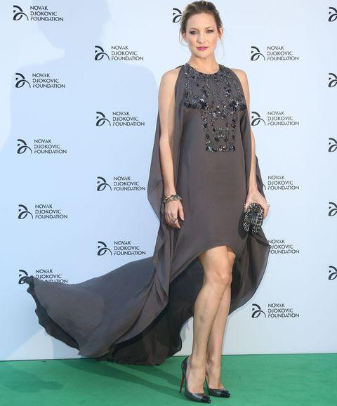 <p><strong>Kate Hudson</strong> fue una de las invitadas más elegantes de la cena gala de la fundación del tenista&nbsp&#x3B;<strong>Novak Djokovic</strong> celebrada en Londres. La actriz escogió un vestido gris oscuro con falda asimétrica efecto cola con detalles de pedrería en el cuerpo de <strong>Elie Saab.</strong> Completó su look con salones y clutch <strong>Louboutin.</strong></p>