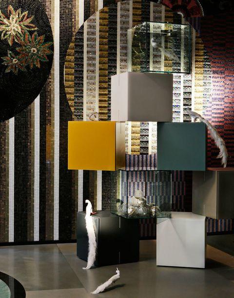 <p>Sobre la <strong>composición</strong> <i>Net</i> formada por 8 cubos de cristal lacado y transparente, 3.973 €, en Lago Store, se posan blancos <strong>pavos reales,</strong> el grande,35,95 €, y pequeños, 25 €/cu, en Baden-Baden, como las bolas en cristal y en plata, desde 18 €/6 ud. En la pared, brillante combinación de mosaico artístico y pixelado de SICIS que aúna formas redondas y verticales con teselas cortadas a mano. Suelo de piedra <i>Serena,</i> Estudio Arqué.</p>