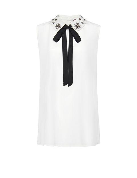 <p>Camisa blanca con cuello joya y lazo (29'95€) de <strong>Mango.</strong></p>