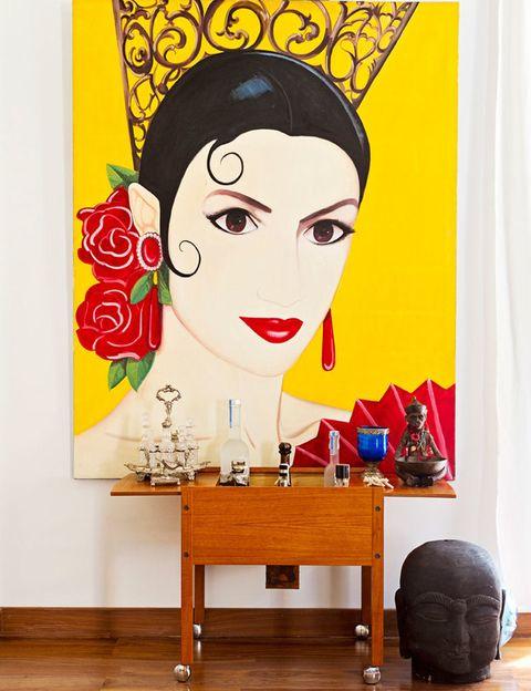<p>En el recibidor, destaca un cuadro de gran formato <i>typical Spanish, </i>de Ortego. Debajo, un carro de bebidas danés de los 50, adquirido en un anticuario. En el suelo, cabeza negra de madera traída de Tailandia.</p>