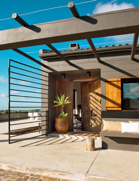 <p>Con un banco de obra pintado de gris y un macetero de Bali, funciona también como porche.</p>