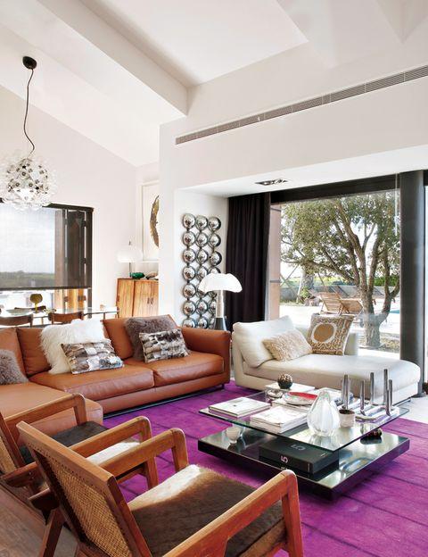 <p>El sofá de cuero, de Pianca, alberga unos graciosos cojines de pelo. Entre éste y la chaise-longue, lámpara <i>Pipistrello,</i> de Gae Aulenti. La mesa de centro es de un anticuario de Pamplona y la alfombra pertenece a la colección<i> Batik,</i> de Carpet Diem.</p>