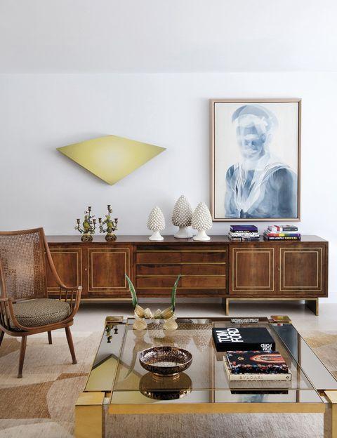 <p>Un aparador retro de madera, de Emilio Rey, una butaca nórdica con respaldo de rejilla años 50 y una mesa de centro en latón cromado, de la década de los 60, dan un marcado carácter al salón. El candelabro de porcelana es de los años 30. En la pared, una obra de Mikeldi Pérez Urkijo, y un cuadro de la artista Sanell Aggenbach. </p>