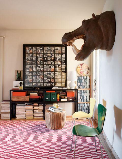 <p>En el recibidor, cabeza de hipopótamo en fibra de vidrio, de Anmoder; alfombra Ponti Red, de Suzanne Sharp para The Rug Company en BSB; sillas Ant, de Jacobsen; consola de wengé y puf de mimbre diseñados por el decorador.</p>