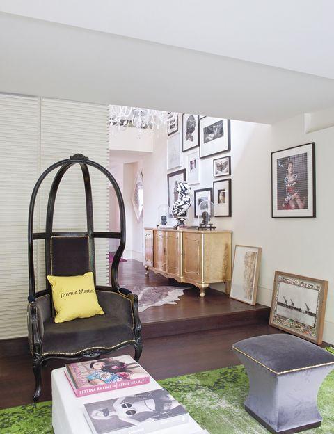 <p>En el corredor de paso del salón al comedor, el protagonista es un aparador dorado pintado a mano sobre el que se apoya el busto<i> Zig Zag,</i> de la serie <i>Shakespeare in disguise,</i> ambos de Jimmie Martin. En la zona de estar la espectacular butaca alta <i>Amazing,</i> de Jimmie Martin, comparte espacio con la mesa de Christian Liaigre y el taburete tapizado, <i>Trento Cube,</i> de The Sofa and Chair Company.</p>