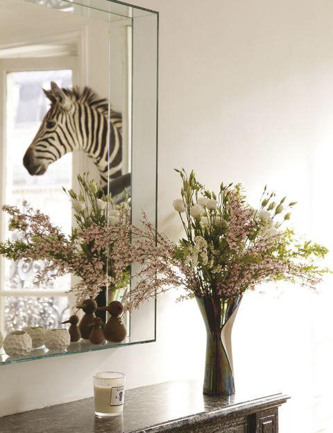 <p>Sobre la chimenea, un espejo con repisa devuelve el reflejo del salón.</p>