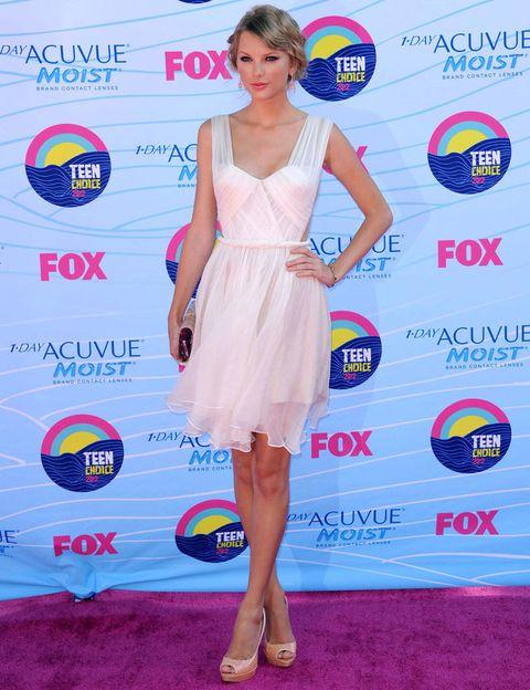 <p><strong>Taylor Swift</strong> con su habitual estilo sfot eligió un little white dress en seda con cortes laterales de <strong>Maria Lucia Hohan</strong>, peep toe nude de&nbsp;<strong>Prada</strong> y un clutch en tono marfil de<strong> Edie Parker</strong>.</p>