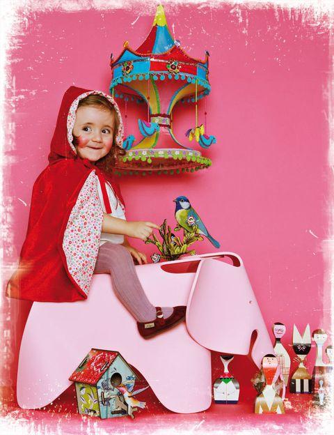 """<p>Nuestra pequeña protagonista, Micaela, luce con estilo su disfraz de <a href=""""http://www.belandsoph.com/"""" target=""""_blank"""">Belandsoph.com</a>, 68 €, montada en el elefante rosa Eames Elephant, 203 €, de los Eames en Vitra. El carrusel de la pared, 201 €, en Usera Usera. En el suelo, varias figuritas de madera modelo <i>Dolls,</i> de Alexander Girard, 108 €/cu, de Vitra; pajarito desmontable y casita decorada desmontable, ambos diseñados por Miho, 23 €/cu, de&nbsp;<a href=""""http://www.belandsoph.com/"""" target=""""_blank"""">Belandsoph.com</a>. En este cuento, no hay lobo feroz y el mundo es de color rosa.&nbsp;</p>"""