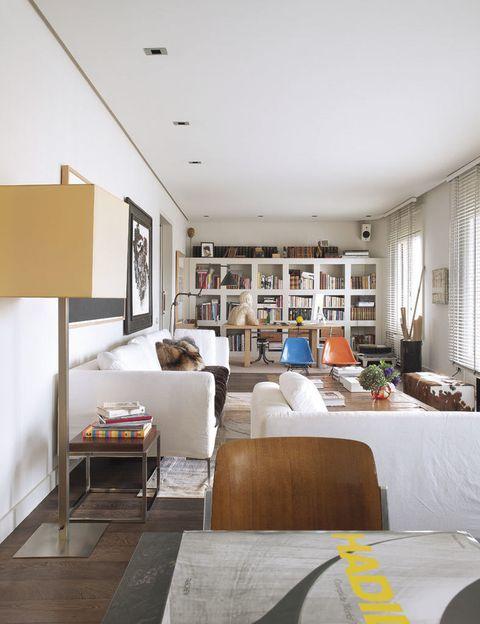 <p>Comedor, salón y escritorio comparten el mismo espacio pintado de blanco. En el sofá, de Antonio Citterio para B&amp;B en Bd, cojines de Goes Home y manta de CoriumCasa, tienda de la que procede el taburete con libros. Éste y la chaise longue delimitan el salón y el comedor.</p>