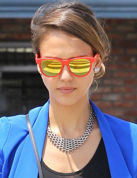<p><strong>Jessica Alba</strong> nos deja con la boca abierta con sus gafas de sol naranjas con los cristales de espejo en tono amarillo, 100% flúor. También nos gusta su collar.</p>