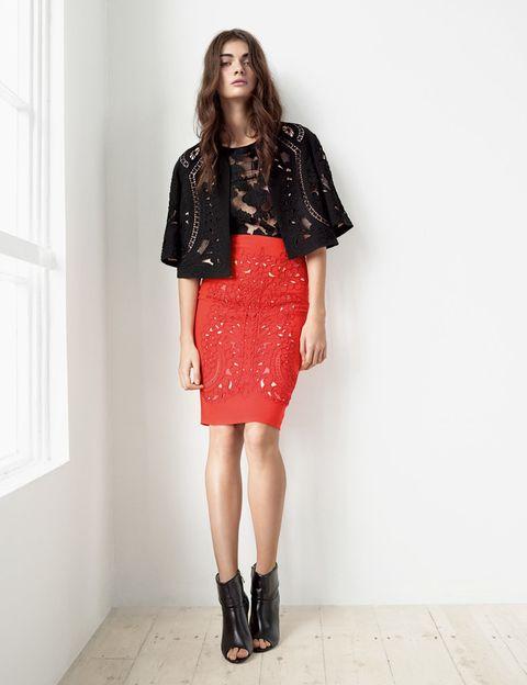 <p>Falda midi en tono coral intenso y troquelada, chaqueta con forma de capa realizada con elaborados calados y camiseta semitransparente holgada.</p>