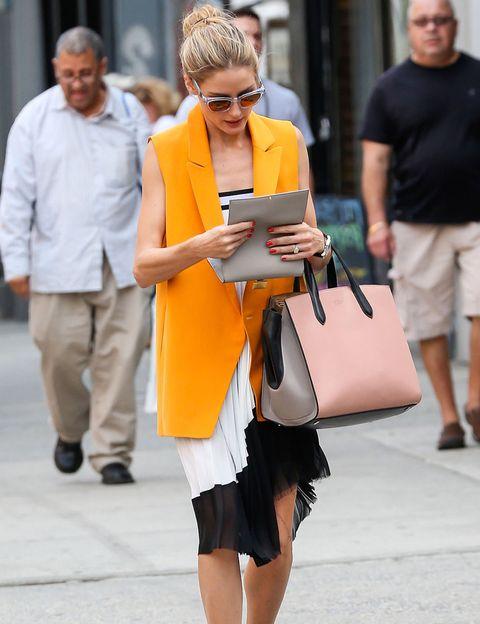 <p>La 'it girl' elige la versión maxi para su chaleco, que elige en color anaranjado y combina con una falda larga que luce subida a modo de vestido.</p>