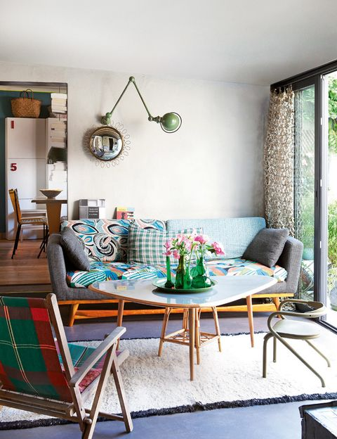 <p>Gracias a inspirados mix: alegres telas originales de Bangkok en el sofá, de Red Edition, una silla de jardín años 50 descubierta en un mercadillo... El suelo de resina revestida de cemento se viste con una estera de color blanco.</p>