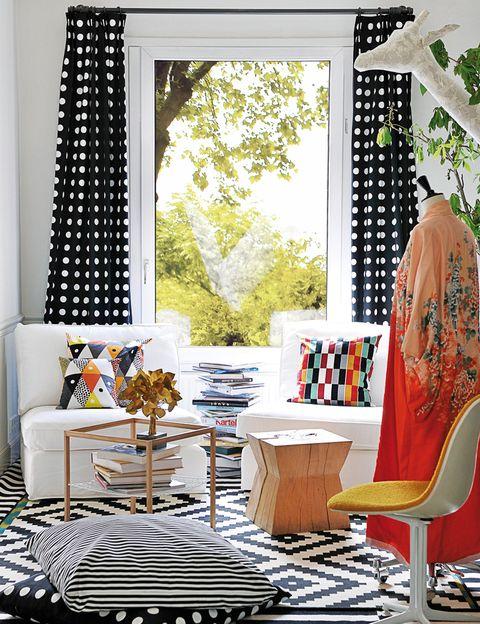<p>Cortinas hechas con el mod. Hildis, como el cojín del suelo. De rayas, Sofia. El del sillón izdo., Hälleknopp, y dcho., Helsinge, todo de Ikea. </p>
