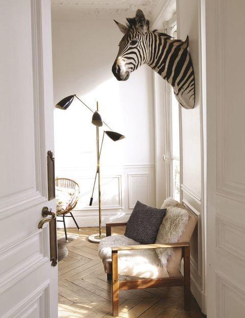 <p>Así es el acceso al salón. La bienvenida la da una cabeza de cebra naturalizada. Debajo, una butaca con alfombra de piel de oveja, similar en Ikea, y al lado, lámpara de pie vintage.</p>