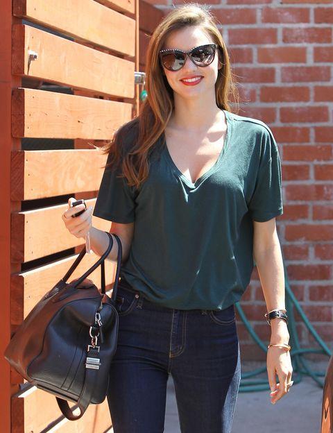 <p>La modelo está estupenda y sencilla combinando una camiseta verde de pico con unos vaqueros. <strong>Miranda Kerr</strong> la remete por dentro y opta por un denim muy ceñido. Los toques más <i>cool</i> los dan los complementos: maxigafas y maxibolso.</p>