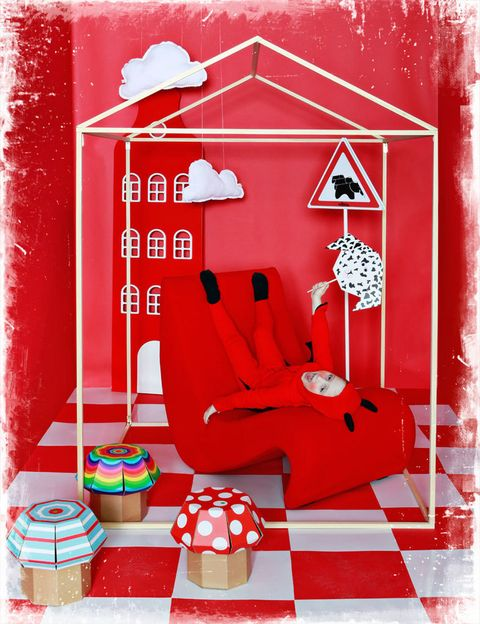 """<p>Desde la butaca <i>Amoebe,</i> de Verner Panton, 1.207 €, de Vitra, Mateo tiene una perfecta visión del""""mundo al revés"""". El disfraz le va que ni pintado, en la mano lleva una máscara de Origami realizada por Elena Saiz, de Spiritu Afin. Al fondo, un armario, que simula una casa típica holandesa de la firma Kast van een Huis, en DM, 998 €, que distribuye Nobodinoz. Los almohadones de nubes, 21,90 € y 24,90 €, en <a href=""""http://www.belandsoph.com/"""" target=""""_blank"""">Belandsoph.com</a>. Taburetes de setas de cartón desmontables, 17,50 €/cu, en Habitat.</p>"""