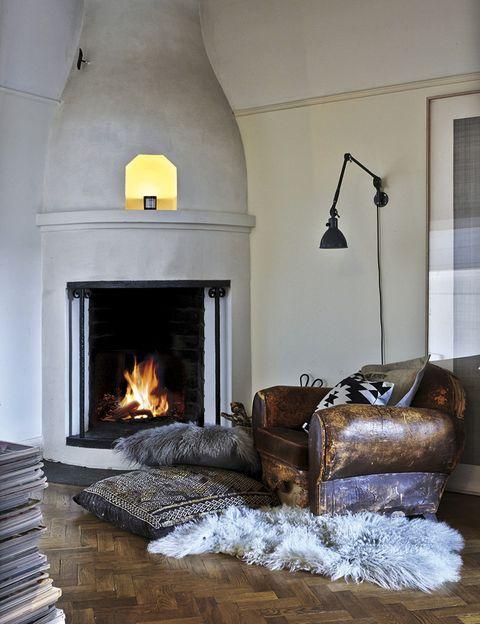 <p>Al lado de la chimenea, un sillón de cuero vintage con una alfombra de pelo y maxicojines étnicos.</p>