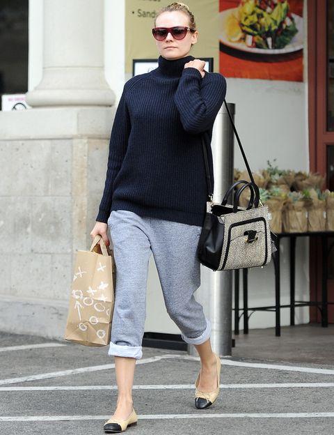 <p>La tendencia sporty cada vez pisa con más fuerza y&nbsp;<strong>Diane Kruger</strong> se apunta con este outfit con pantalones grises de algodón, jersey de punto navy, bailarinas bicolor y bolso de piel.&nbsp;</p>
