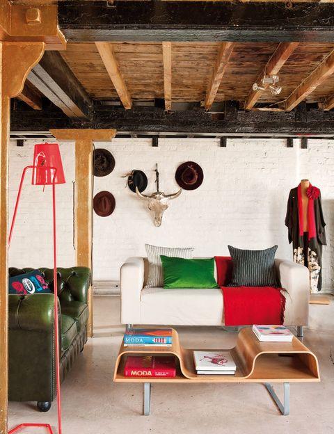 <p>En el salón, sobre el sofá <i>Klippan,</i> de Ikea, manta, de Hermès&#x3B; cojines de rayas en blanco y negro, de Dominique Kieffer, en Dolz, y verde, de MCH. En la pared, cabeza de vaca, de Katrina Phillips.</p>