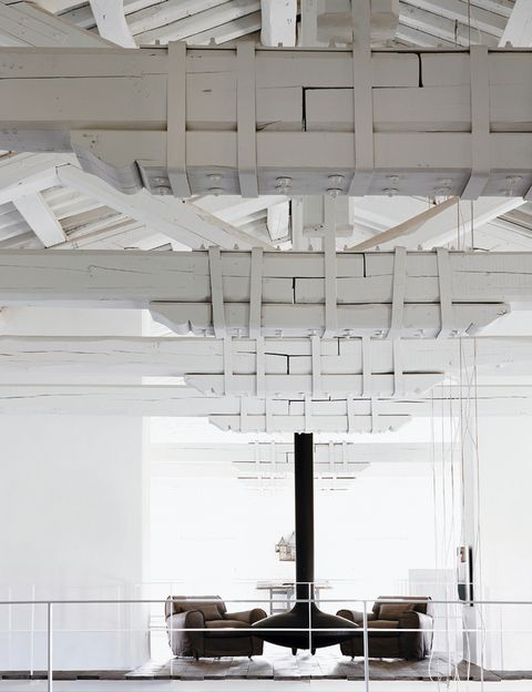 <p>Como flotando en el aire, la chimenea suspendida de Focus pone un contraste oscuro en medio de la blanca trama de las vigas en la planta superior. La rodean dos sillones grises <i>Housse</i> diseñados por Paola Navone para la firma Baxter.</p>