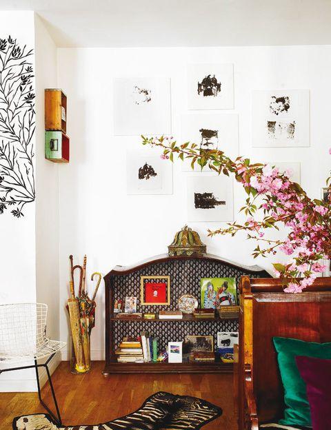 <p>En un rincón del salón, se utiliza como librería la parte superior de un aparador recuperado con la trasera revestida con papel pintado. En la pared, una composición formada por imágenes de Venecia. </p>